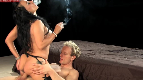 The brunette smokes and actively fucks with the man