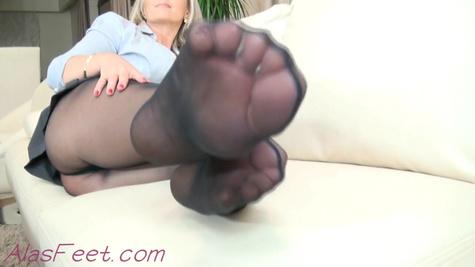 Зрелая потаскуха в черных колготках показывает свои ножки на диване