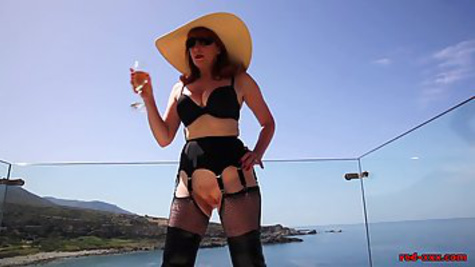 A mature bitch in black stockings goes out onto the balcony and masturbates her vagina with a bottle
