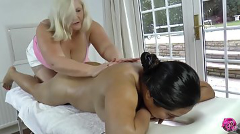 Fat woman makes massage to girl and caresses her body on the table