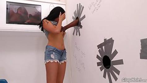 Женщина трахается с негром через дыру в стене и сосет его член