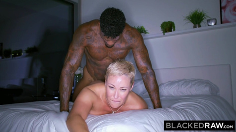 A mature woman with short hair relaxes and gives a black man