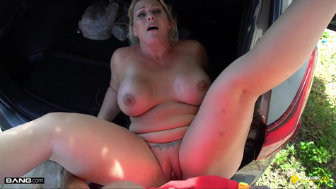 A mature slut fucks on the street, lying in the trunk of a car