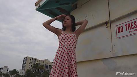 Худенькая азиатка на море поднимает сарафан и ласкает киску