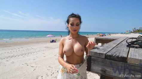 Hot woman with big tits strips naked on the beach and shows her sexy body in front of the camera