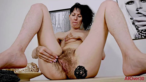 Mature brunette woman is spreading her legs wide open to show her bushy pussy to the camera