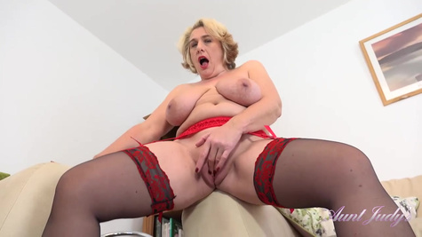 Busty granny, Camilla is wearing erotic stockings and garter belt while masturbating in her home