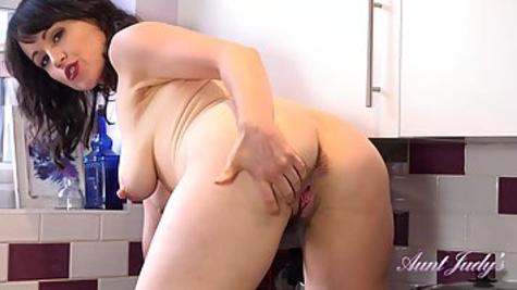 Зрелая и толстая баба мастурбирует пизду на кухне перед камерой