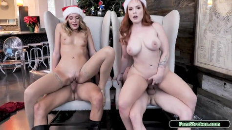 Two horny ladies with Santa hats are riding rock hard dicks and trying a group sex in front of a Christmas tree