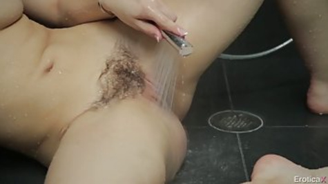 Brunette chick is completely naked in the bathroom and masturbating her hairy pussy with water
