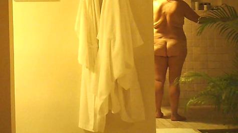 Сморщенная толстая женщина подмывается